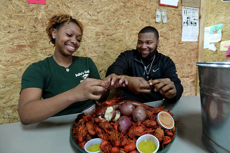 Jasmine Bradley and Raydell Davis of Houston joke with one another as they dig in to the first order served up at JuJu's Cajun Crawfish Shak in Fannett on the opening day of the crawfish season Friday. Bradley will likely trek to Fannett every two weeks or more often to satisfy her crawfish cravings and support JuJu's, her favorite crawfish stop. Mudbug enthusiasts signed in and awaited the opening of the doors to get their first taste of the boiled crustacean's, each seasoned and filled with sides to order like potatoes, corn cobs, and sausage. Within minutes of opening, the picnic tables inside were filled and the hooks on which aprons hung were bare. Crawfish season this year started slightly later than normal due to the unusually cold weather that lingered in the region throughout the past month.  Photo taken Friday, February 9, 2018 Kim Brent/The Enterprise Photo: Kim Brent / BEN
