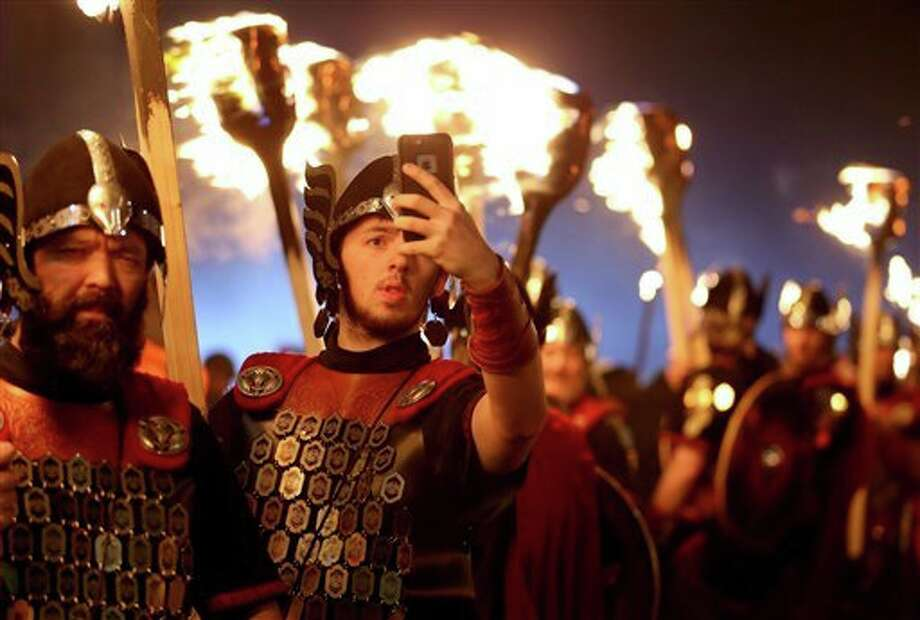 Jane Barlow | PA (AP) A member of Shetlands Up Helly Aa Vikings takes a selfie photo, as they are dressed to lead the opening event of Edinburghs Hogmanay (New Year) celebrations with the traditional Torchlight Procession in Edinburgh, Scotland.