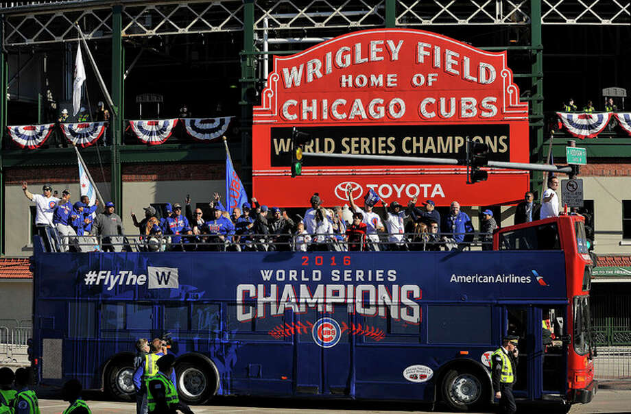 Paul Beaty | AP A bus carrying Chicago Cubs players, family and friends passes Wrigley Field during a parade honoring the World Series champion baseball team in Chicago. The Cubs first World Series title since 1908 is the runaway winner for top Illinois story and also top sports story of 2016.