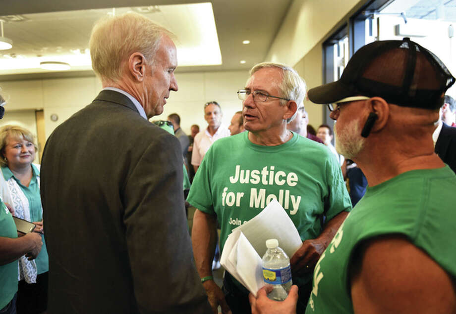 """Byron Hetzler   The Southern Illinoisan (AP) Gov. Bruce Rauner speaks with Larry Young, father of Molly Young, after Rauner signed the two bills collectively known as """"Molly's Law"""" in Carbondale. The law that took effect Sunday extends the statute of limitations from two years to five on bringing wrongful death lawsuits and increase fines for public bodies that don't comply with court orders to release information. """"Molly's Law"""" is named after Molly Young, a Carbondale woman fatally shot in 2012 and found in her ex-boyfriend's apartment."""