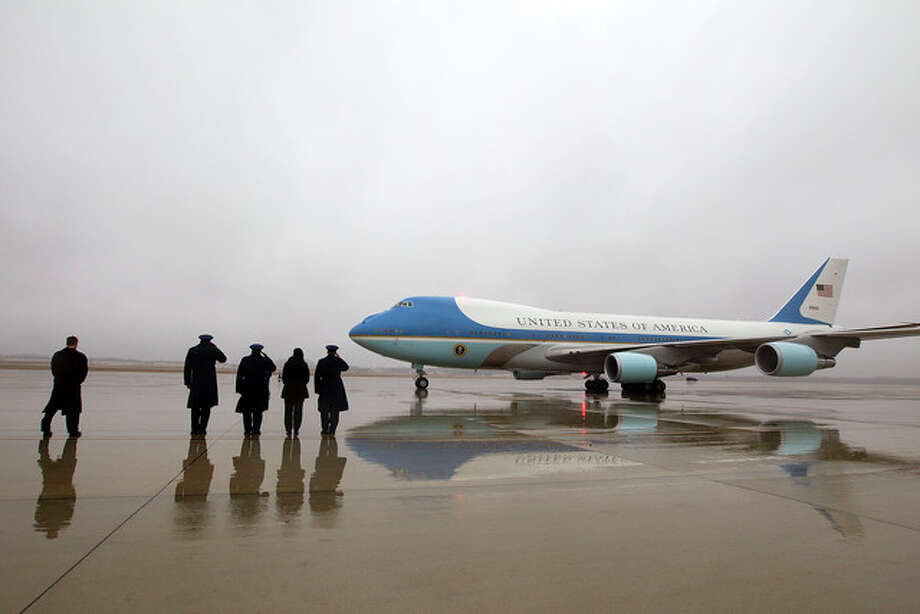 Jose Luis Magana |AP Military personnel salute Monday as Air Force One, carrying President Barack Obama and his family, arrives at Andrews Air Force Base. The president and his family were returning from a vacation in Hawaii.