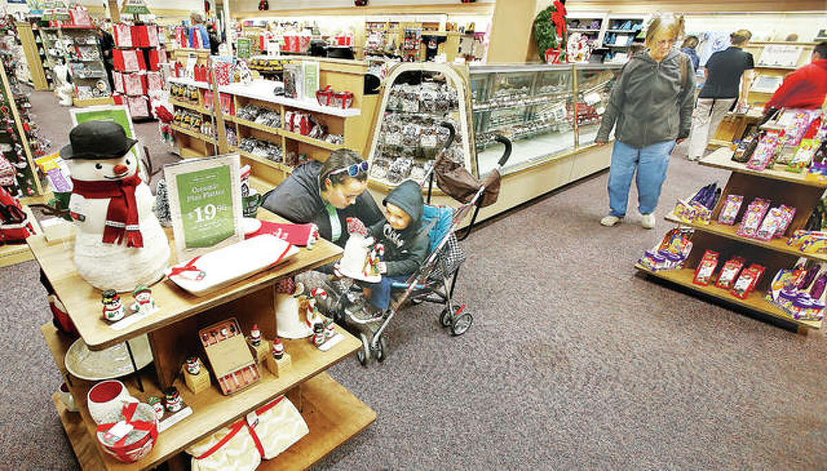 A woman shows her baby a Christmas snowman Friday at the new Jan's Hallmark store in Alton Square Mall Friday during its Holiday Open House. The event is the store's first since it opened about one week ago and goes through Sunday.