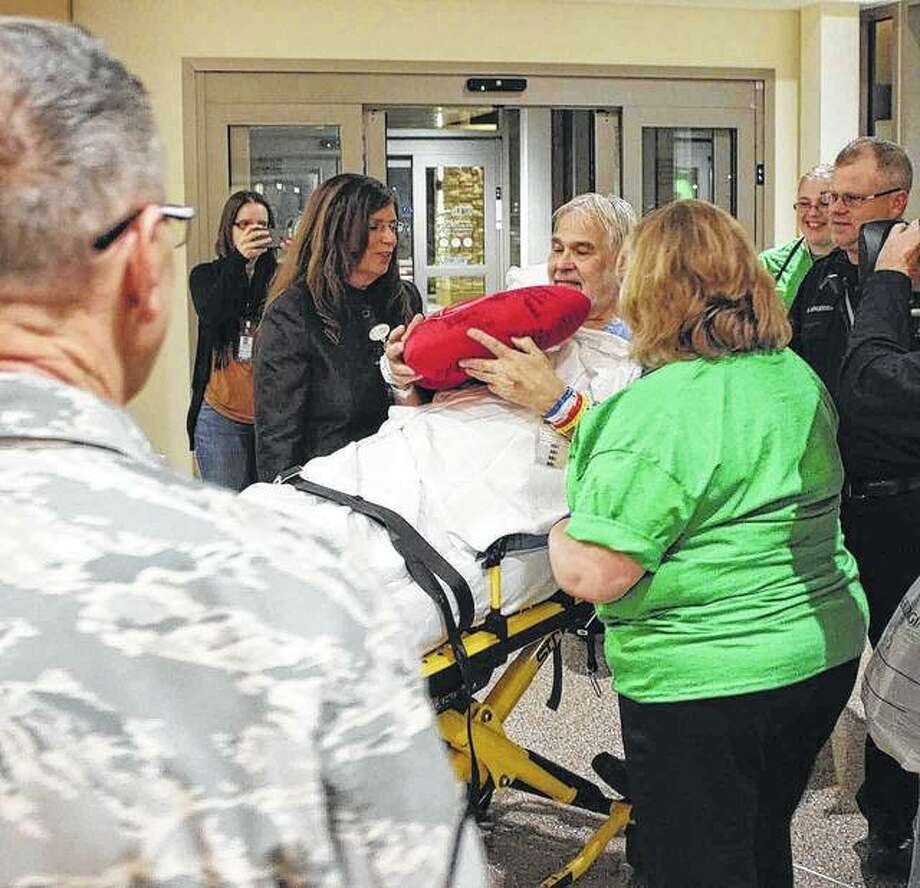 Daniel Thelen of Belleville was pleased to be the first patient admitted to the new HSHS St. Elizabeth's Hospital in O'Fallon. He is surrounded by HSHS St. Elizabeth's clinical staff and Scott Air Force Base personnel assisting with the move.