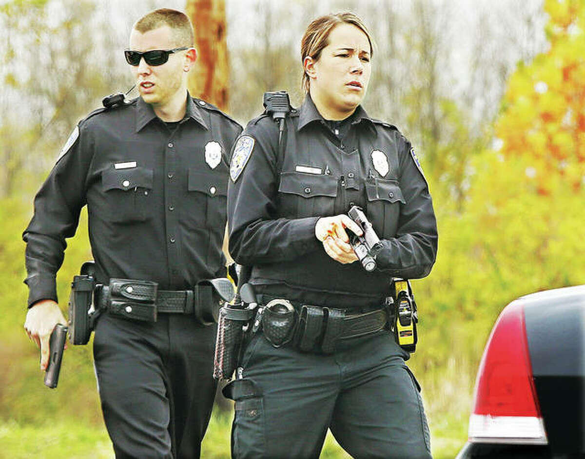 Alton police officer Kim Lutman, right, and officer Clinton McNear, pistols drawn, move in to check the car for additional occupants and check the trunk of the car following the arrest of the three men.