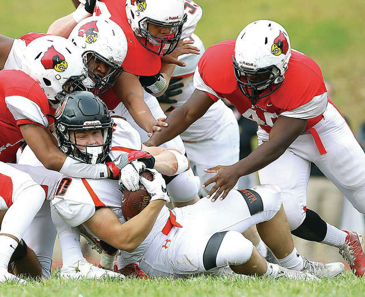 Lincoln-Way West's Caleb Marconi, is brought down by, from left, Alton's Rashad Williams, Charles Miller, Izeal Terrell and Cortez Jefferson in Saturday's 7A West win at Public School Stadium. Marconi and several other West players were coached in New Lenox youth football by Alton native Perry Plarski and his son, Sean Plarski.