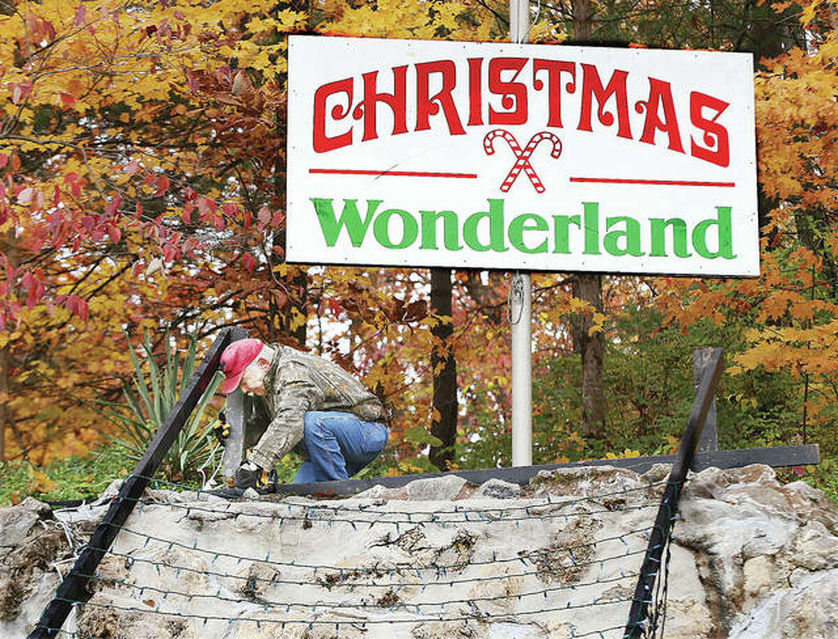 A member of the Grandpa Gang works on the waterfall lights in Rock Spring Park Tuesday morning following an overnight theft of around 1,500 feet of copper wire and vandalism to some of the trailers the volunteers use for the annual Christmas Wonderland display.