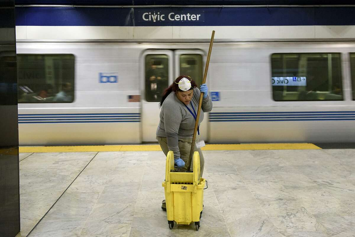 A train passes by as BART systems services member Amisha Hudson squeezes out her mop while cleaning on the platform at the Civic Center BART station in San Francisco, CA, on Friday February 9, 2018.