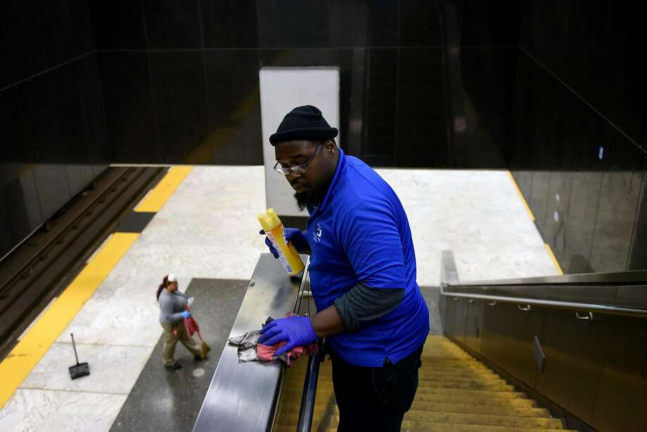 BART systems services member Dantone Sharkey wipes off a handrail on a stairway as co-worker Amisha Hudson sweeps the platform below at the Civic Center Station. Photo: Michael Short, Special To The Chronicle