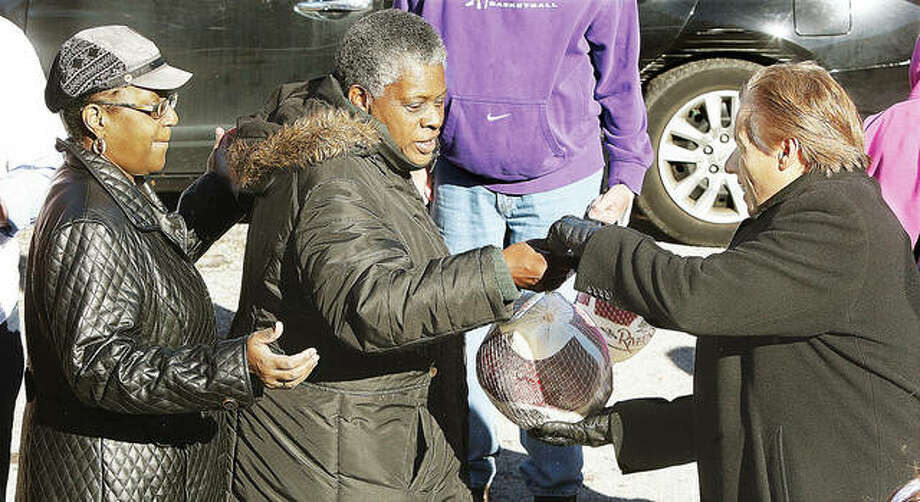 In this photo from 2015, Alton Mayor Brant Walker, right, helps hand out frozen turkeys to those who lined up to get a free one at the Salvation Army. TorHoerman Law will hold its 4th annual turkey giveaway Nov. 16. Photo: John Badman | The Telegraph