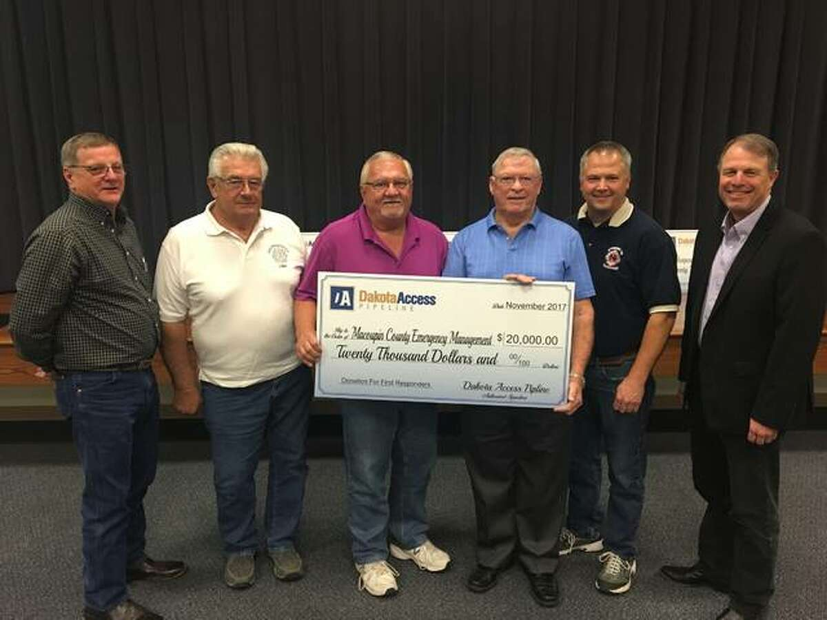 Macoupin County leaders accept a check for $20,000 for first responders from Dakota Access Pipeline officials.