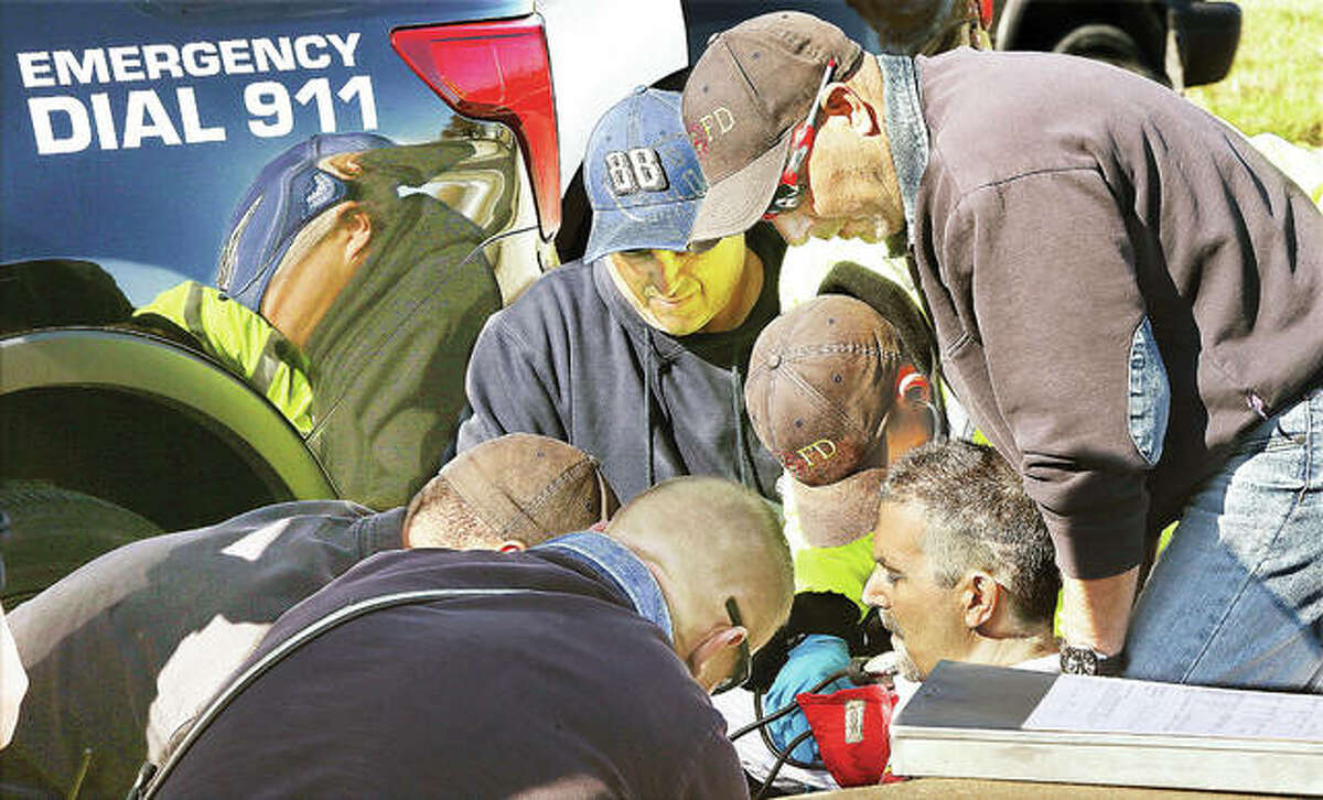 The passenger of the Equinox, lower right, was handcuffed and put in a police car before being found by firefighters unconscious and not breathing. Wood River firefighters gather around, where he was revived with two nasal doses of Narcan they administered before he, too, was transported to a local hospital by ambulance.