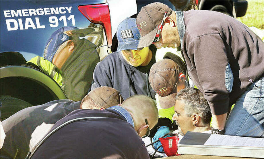 The passenger of the Equinox, lower right, was handcuffed and put in a police car before being found by firefighters unconscious and not breathing. Wood River firefighters gather around, where he was revived with two nasal doses of Narcan they administered before he, too, was transported to a local hospital by ambulance. Photo: John Badman|The Telegraph