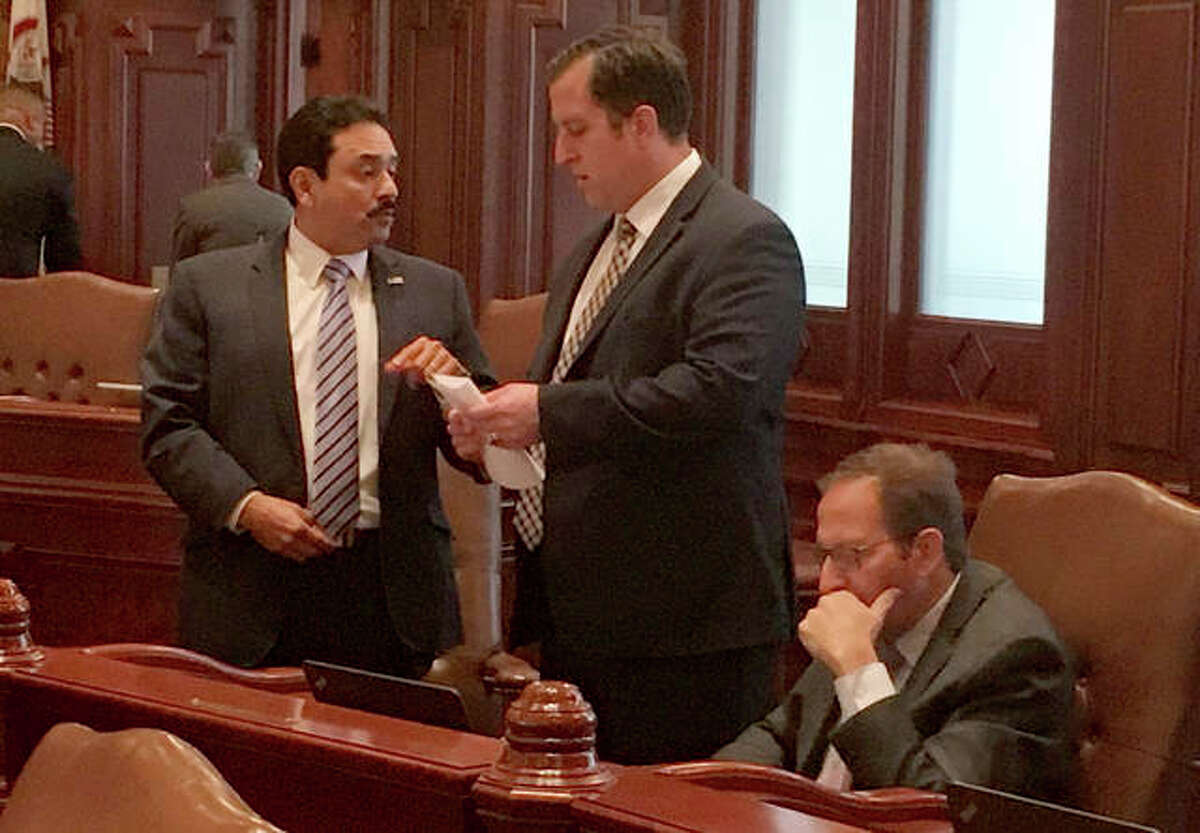 Democratic Senators Tony Munoz D-Chicago, left, and Michael Hastings D-Tinley Park, speak on the floor of the Illinois Senate as Sen. Ira Silverstien, D-Chicago, sits nearby Tuesday Nov. 7, 2017, in Springfield, Ill. The Senate voted to expand power of the newly appointed inspector general to allow her to investigate existing complaints, including one filed last November by legislative activist Denise Rotheimer against Silverstein.