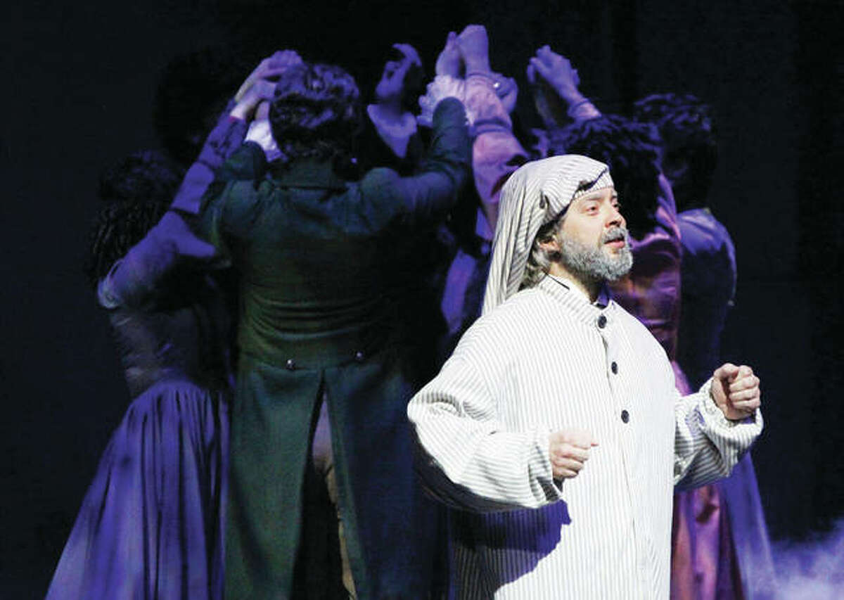 """Ebenezer Scrooge sings about Christmas memories while revelers, from Fezziwig's party, dance behind him in """"A Dickens Christmas Carol"""" at Silver Dollar City in Branson. The musical is entering its 15th year at the theme park."""