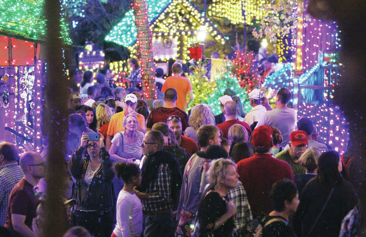 """People wander through the new """"Christmas in Midtown"""" light display at Silver Dollar City in Branson. The park added approximately 1.5 million new Christmas lights for the display."""