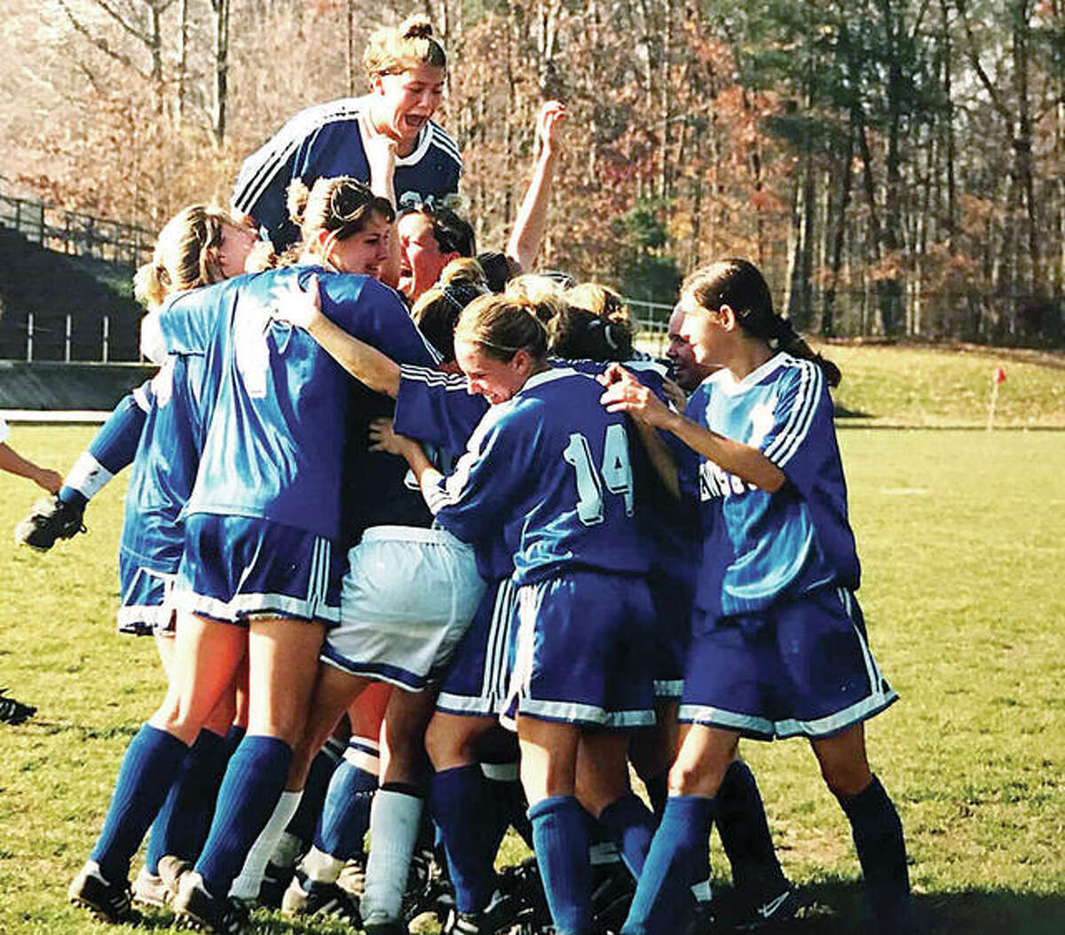 Angie Bode, top, jumps on her celebrating LCCC teammates after they won the NJCAA women's national soccer championship in Baltimore.