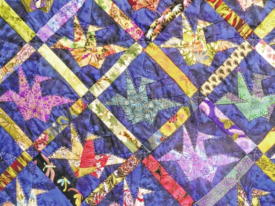 The colorful patterns of a quilt by Laverne Roy fill a display at the Jacksonville Public Library. Photo: Jeannie Hemphill | Reader Photo