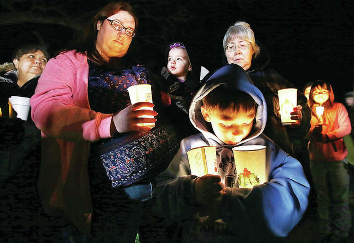 Raymond Bruner, 6, who lived across the street from 6-year-old Liam Roberts, looks into his candles during a vigil at the Jersey County Fairgrounds Thursday evening to remember the boy who allegedly starved to death in his own home. His father and stepmother have been charged with first degree murder in connection with his death. Liam weighed only 17 pounds upon his death. A representative for neighbors came forward to say they never even knew there were children there, no toys in the yard, no clues as to what was happening in their neighborhood.