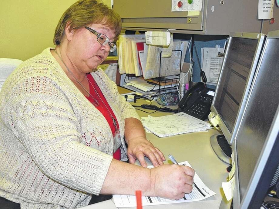 Rosemary Hopkins, a reimbursement specialist at Passavant Area Hospital, fills out insurance forms Thursday. Photo: Nick Draper | Journal-Courier