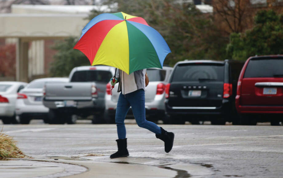 Mike Simons | Tulsa World (AP) A pedestrian shields herself from freezing rain Friday as a winter storm that pounded northern California descended upon the Midwest, packing dangerous ice accumulations and heavy rain.