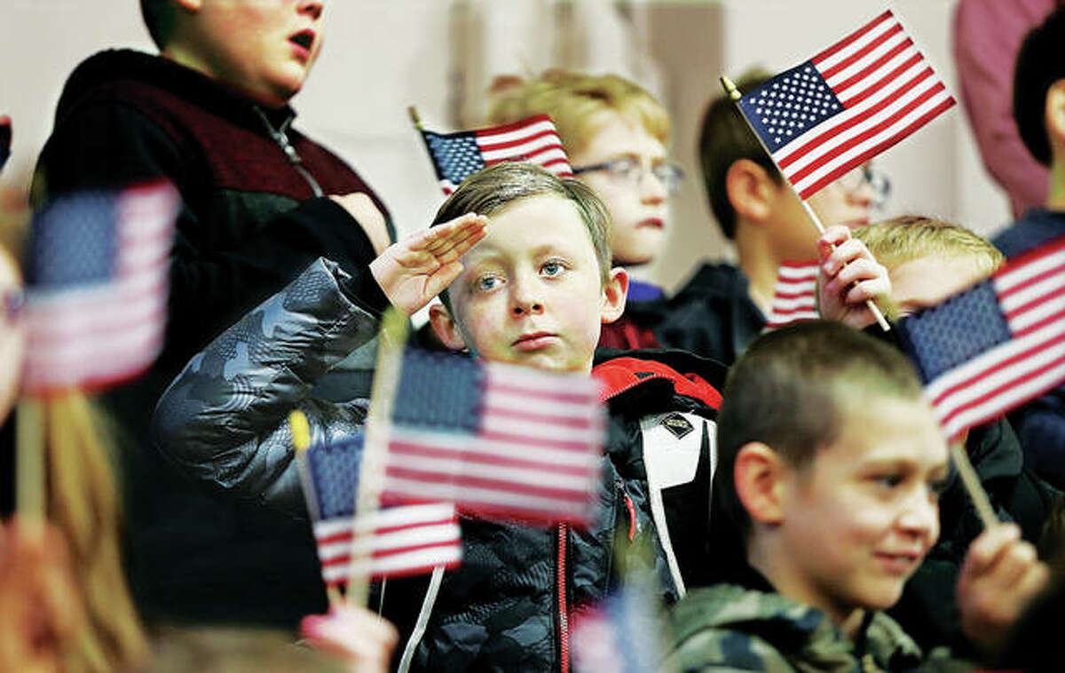 A student at North Elementary School in Godfrey salutes the veterans who attended a brief ceremony in their honor Friday morning as his fellow students wave their small flags. Veterans from Lewis and Clark Community College came over to be presented Veterans Day cards made by students and were present for the Pledge of Allegiance and the singing of the National Anthem by the school's fifth-grade chorus.