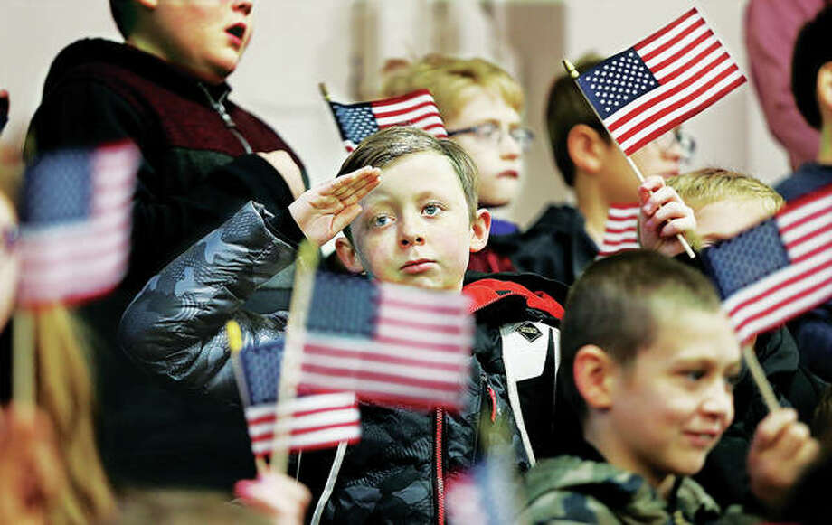 A student at North Elementary School in Godfrey salutes the veterans who attended a brief ceremony in their honor Friday morning as his fellow students wave their small flags. Veterans from Lewis and Clark Community College came over to be presented Veterans Day cards made by students and were present for the Pledge of Allegiance and the singing of the National Anthem by the school's fifth-grade chorus. Photo: Photos By John Badman | The Telegraph