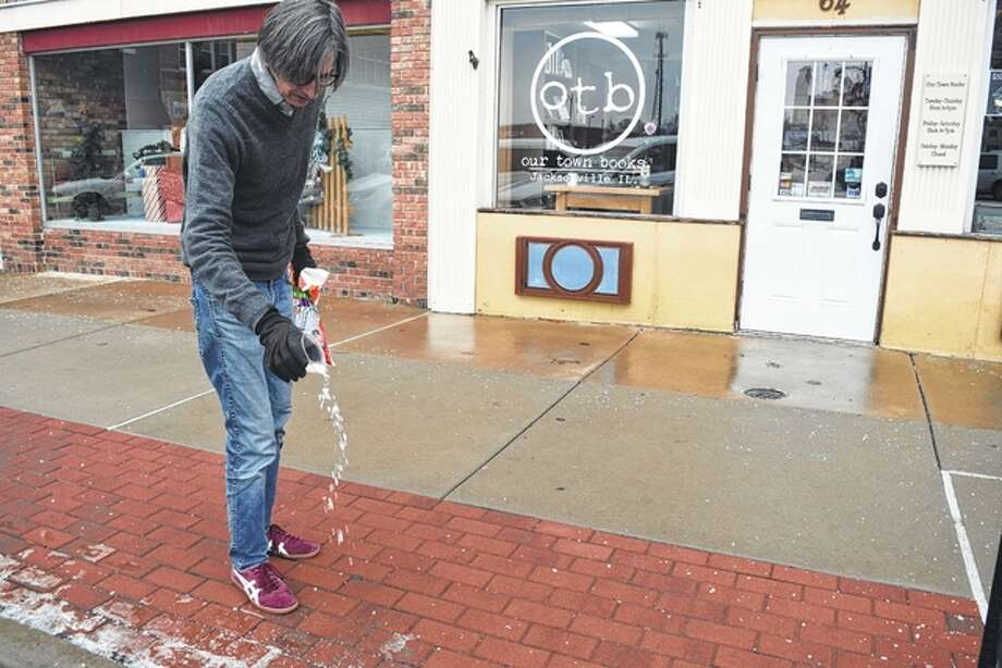 Our Town Books owner Andy Mitchell sprinkles ice melt Saturday on the sidewalk in front of his business on the east side of Jacksonville's downtown square. The Jacksonville area received a thin coating of ice Friday and Saturday, while some areas to the west and south saw more significant accumulation. Photo: Greg Olson | Journal-Courier