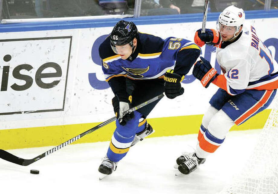 The Blues' Colton Parayko, left, skates around New York Islanders' Josh Bailey Saturday night in St. Louis. Photo: AP