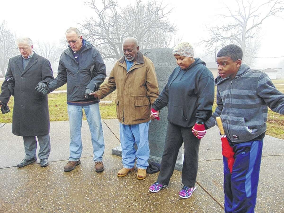 Outreach minister Alan Bradish leads the closing prayer during the annual Martin Luther King Jr. Day ceremony at the King Memorial in Community Park.