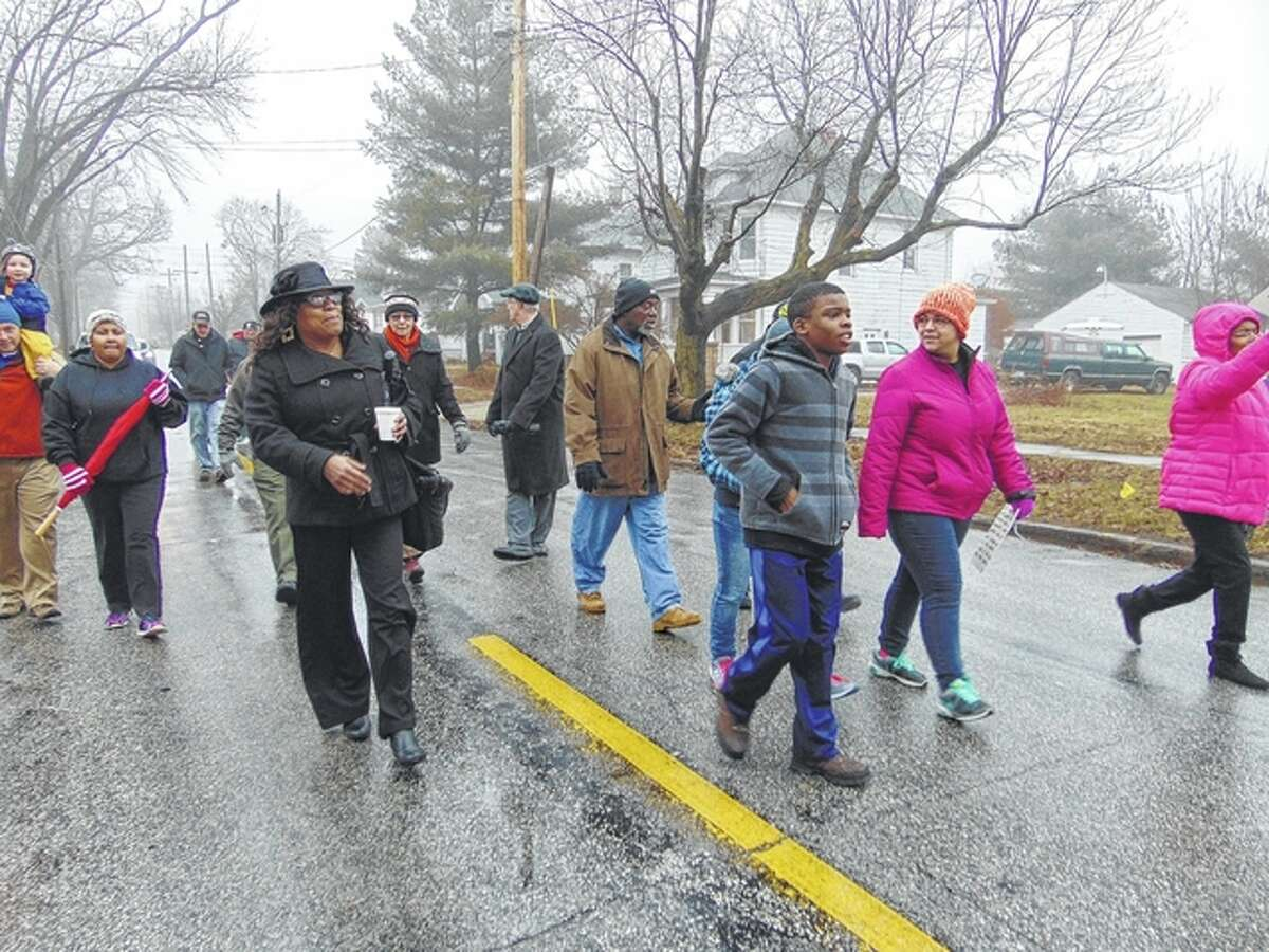 Community members march Monday in honor of the late civil rights activist Martin Luther King Jr. despite a cold, steady rain falling.