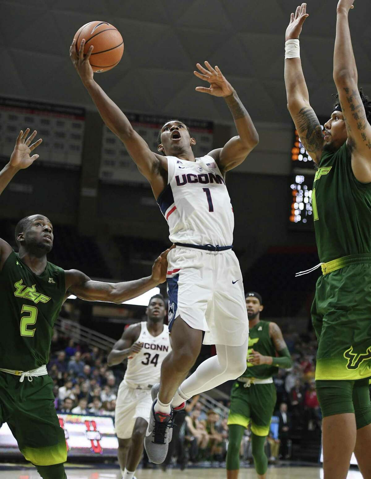 UConn's Christian Vital, center, goes up for a basket as South Florida's Terrence Samuel, left, and Isaiah Manderson, right, defend during the second half on Feb. 7 in Storrs.