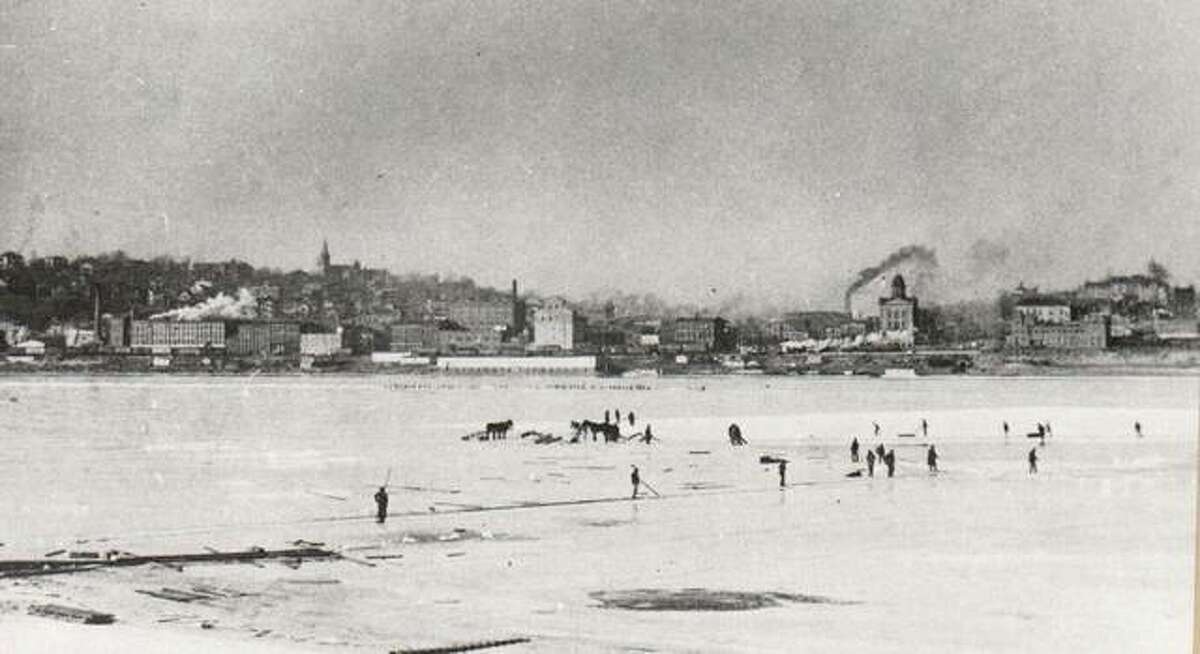 """Winter's freezing weather affected commerce in Alton in 1900 just as it does today. Steamers were unable to travel the rivers and most were sent south to avoid the ice and the possibility of being crushed in the hug ice jams that formed on the upper stretches of the Mississippi. Ice on the Mississippi did, however, provide the town with ice for storage before the first ice plants were built. Ice harvesting was an important winter activity. Long plank """"bridges"""" were laid across the ice for the ice-cutters to reach the island in the Mississippi. They used a variety of tools and sleds to transport the ice to storage. The Alton City Hall can be seen in the background."""