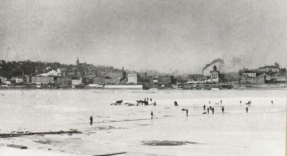 "Winter's freezing weather affected commerce in Alton in 1900 just as it does today. Steamers were unable to travel the rivers and most were sent south to avoid the ice and the possibility of being crushed in the hug ice jams that formed on the upper stretches of the Mississippi. Ice on the Mississippi did, however, provide the town with ice for storage before the first ice plants were built. Ice harvesting was an important winter activity. Long plank ""bridges"" were laid across the ice for the ice-cutters to reach the island in the Mississippi. They used a variety of tools and sleds to transport the ice to storage. The Alton City Hall can be seen in the background. Photo: File Photo"