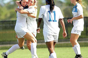 Megan McDonald, left, hugs teammate Kassidy Louvall after Louvall scored a first-half goal Friday at the NJCAA National Tournament. Also pictured are LC's Senate Letsie (11) and Aivia Dubois.