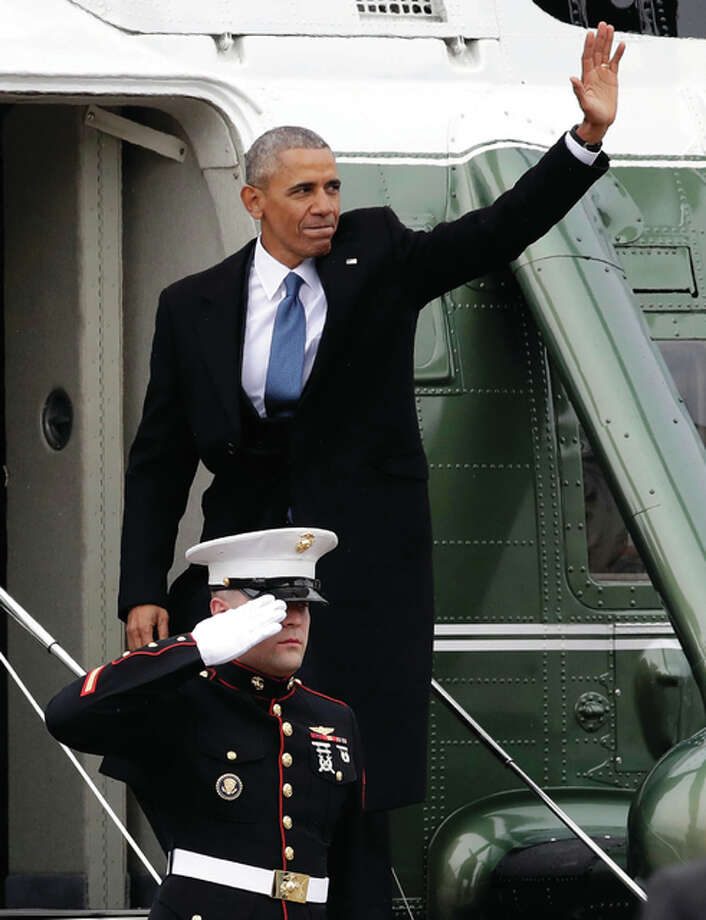 Evan Vucci | AP Former President Barack Obama waves as he boards a helicopter on the East Front of the Capitol on Friday after Donald Trump was inaugurated.
