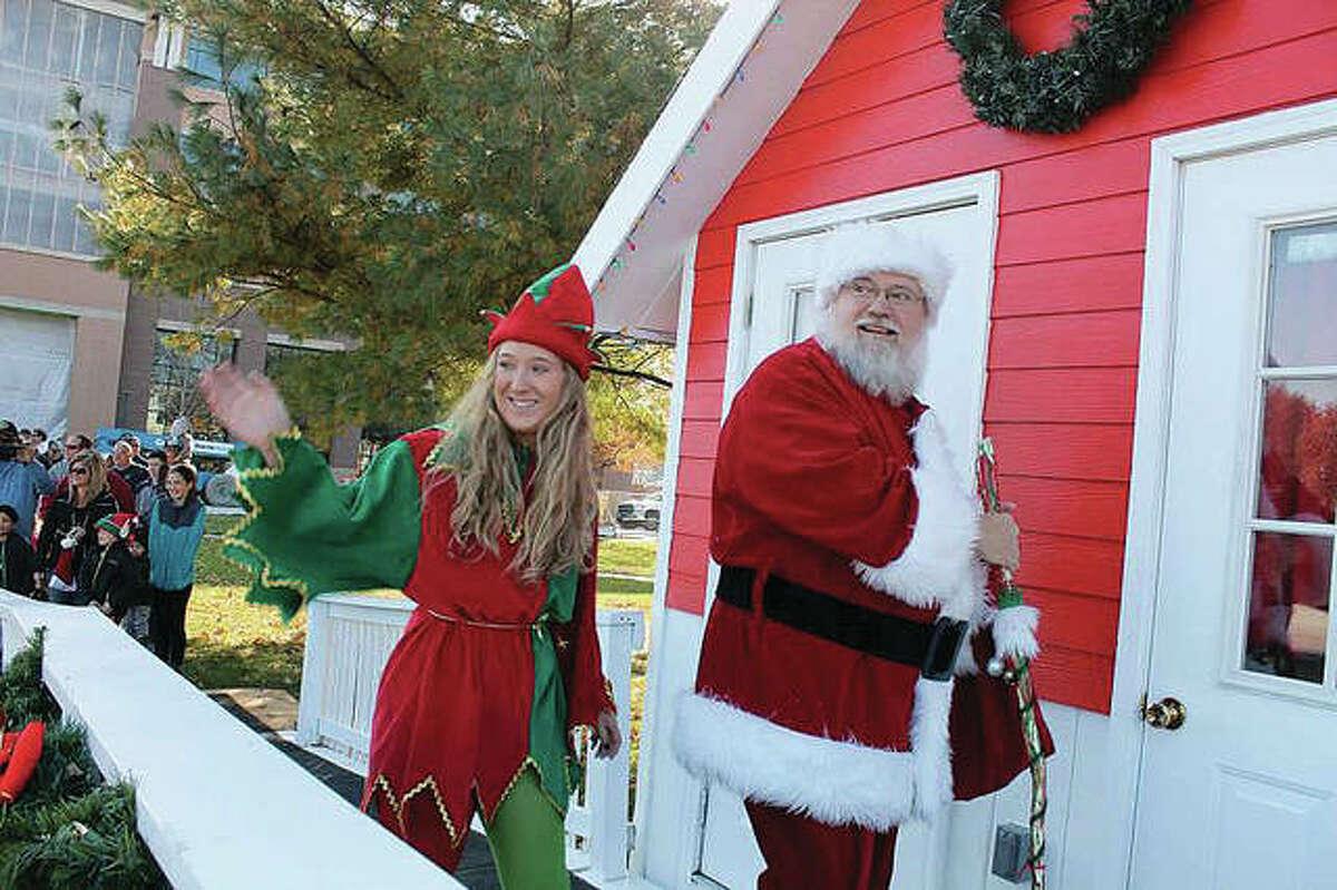 Santa Claus and his elf enter the City Park Santa House.