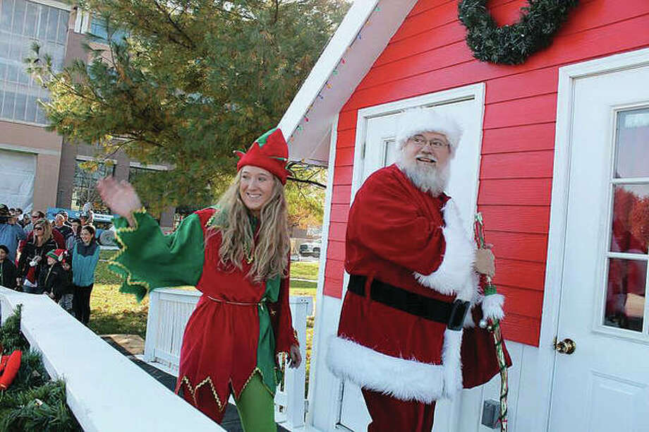 Santa Claus and his elf enter the City Park Santa House. Photo: Bill Tucker| For The Telegraph