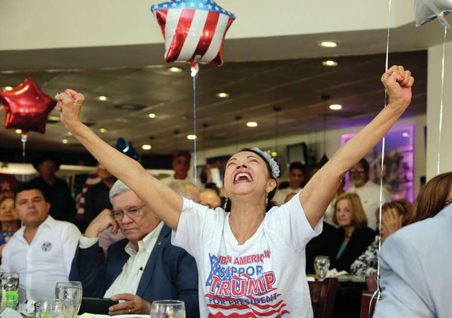 Lynne Sladky | AP Julia del Rio cheers as she watches a televised broadcast of the presidential inauguration of Donald Trump on Friday during a watch party organized in Miami.