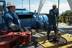 (left to right) Schlumberger's trainees Jerry Jensen (cq) and Jeffrey Murray (cq) practice handling the equipment on the Genesis Drilling Test Facility where employees train with a real life size drilling simulator which was commissioned in 1986 at company's U.S. headquarters in Sugar Land and continues to train on Wednesday, September 27, 2006. Schlumberger is the world's largest oilfield services company and has had a local presence since the 1930s; it recently consolidated its New York offices in Houston. Schlumberger is coming off a record quarter and anticipates solid financial growth as profit-rich oil companies invest more in exploration. Photo by Mayra Beltran / Houston Chronicle