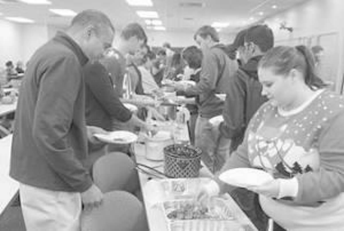 Students line up to sample a diversity of food items at the SOP Thanksgiving Potluck. Considering his options is SOP Dean Gireesh Gupchup, PhD (on the left).