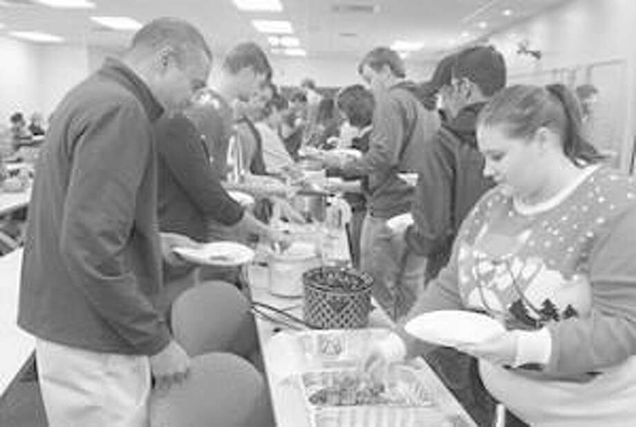 Students line up to sample a diversity of food items at the SOP Thanksgiving Potluck. Considering his options is SOP Dean Gireesh Gupchup, PhD (on the left). Photo: For The Telegraph
