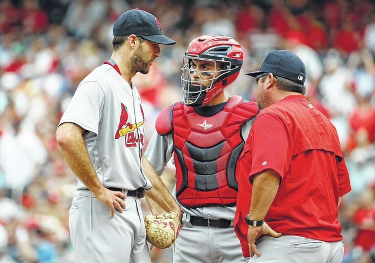 Former Cardinals pitching coach Derek Lilliquist, right has been hired to be the pitching coach for the Washington Nationals. Lilliquist is shown talking with Cards starting pitcher Michael Wacha, left, catcher Eric Fryer during a 2016 game.