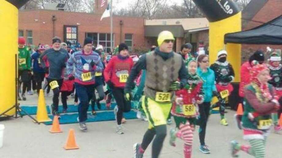 Participants dash from the starting line during last year's CHRISTmas Ugly Sweater Dash 5K. Photo: For The Telegraph