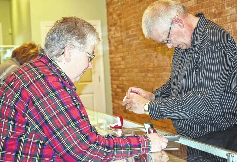 Joyce Clark of Carrollton looks at a pair of earrings with the help of Tim Allen, manager of Nims Jewelry in Carrollton. Nims will be closing at the end of the month.