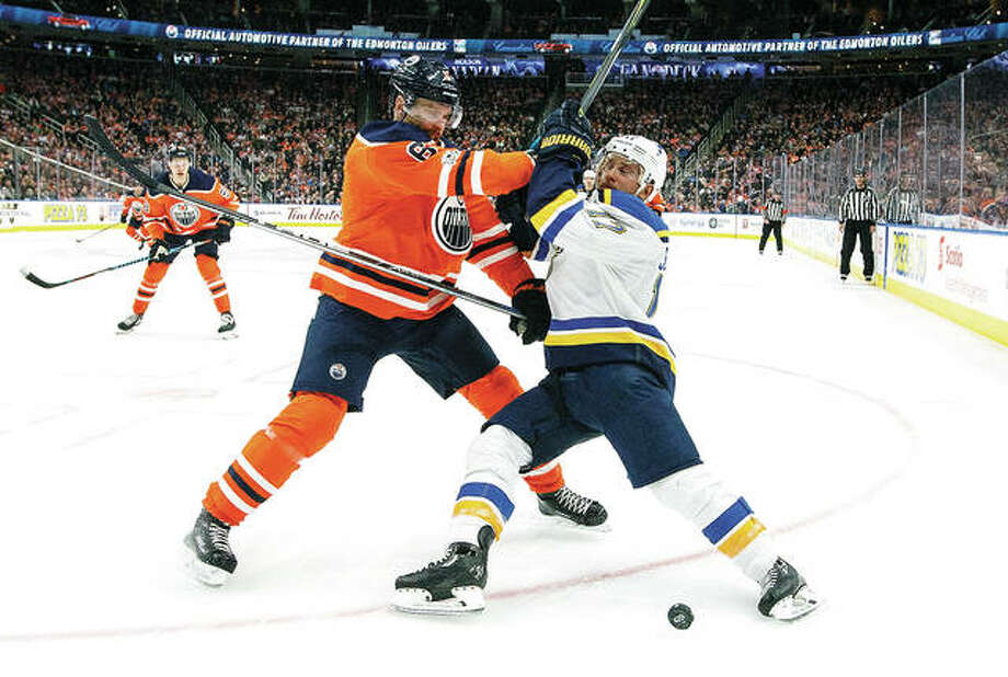 The Blues' Jaden Schwartz (17) and Edmonton Oilers' Adam Larsson vie for the puck Thursday night in Edmonton, Alberta. Photo: AP