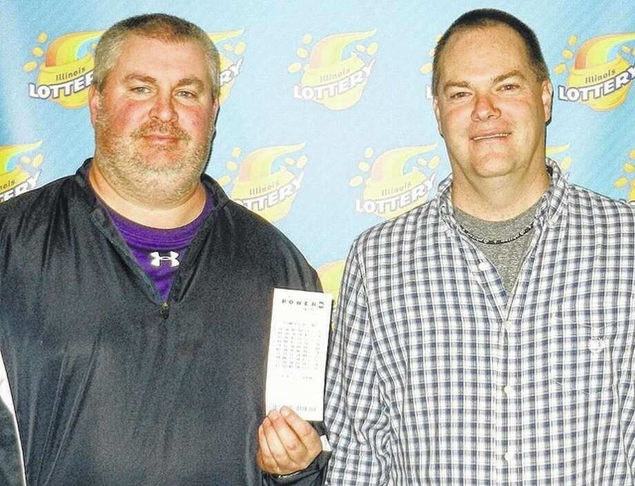 Photo provided Patrick Gibson (left) and James Martin of Jacksonville hold the lottery ticket that won $1 million for a group of 23 people.