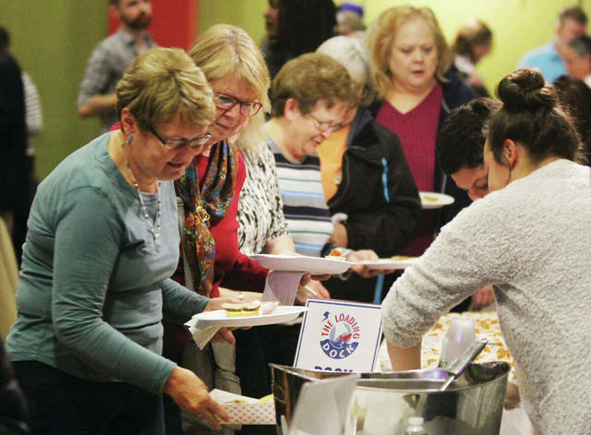 People lineup for samples of food from local restaurants at Taste of Downtown, an annual fundraiser for Alton Main Street, held Thursday in the Music Hall at the Argosy Casino. More than 300 people came out to sample offerings from more than a dozen local restaurants and caterers.