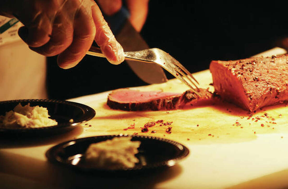 Pepper tenderloin from Journey, a restaurant at the Argosy Casino, is cut by a server at Taste of Downtown, an annual fundraiser for Alton Main Street, held Thursday in the Music Hall at the casino.