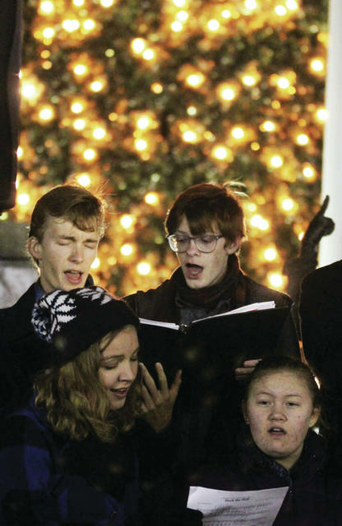 Alton High School Chamber Singers members Kevin Neace, clockwise from top left, Austin Turnbull, Dominique Reinier and Audrey Neace perform Christmas carols during the 23rd annual Christmas Tree Lighting in Lincoln-Douglas Square in downtown Alton. The ceremony drew about 250 people, and is sponsored by Alton Main Street.