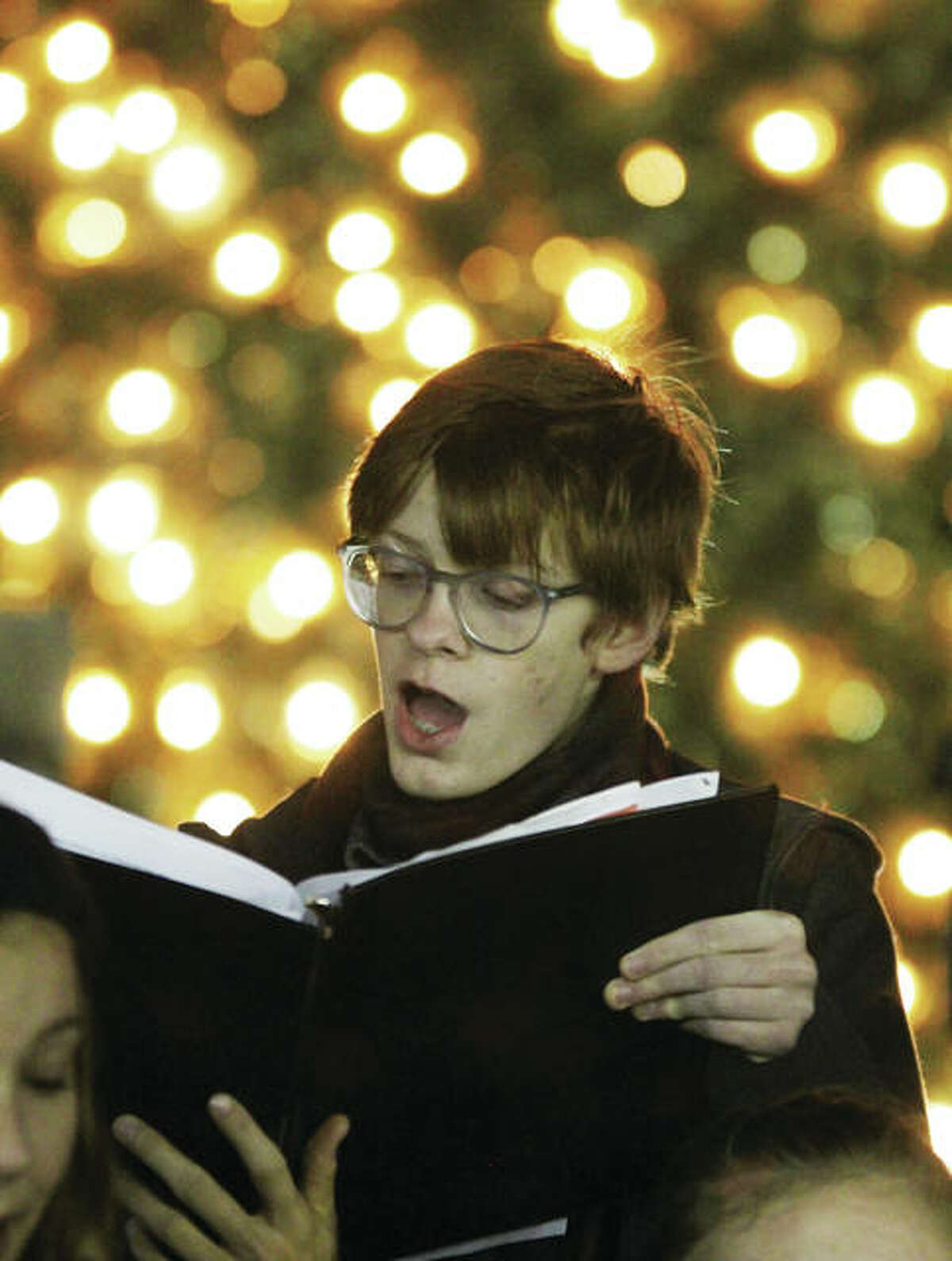 Austin Turnbull, a member of the Alton High School Chamber Singers, sings Christmas carols during the 23rd annual Christmas Tree Lighting in Lincoln-Douglas Square in downtown Alton. The ceremony drew about 250 people, and is sponsored by Alton Main Street.